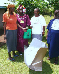 Elizabeth Oranga (center) earns income by demonstrating and selling solar cookers in her community